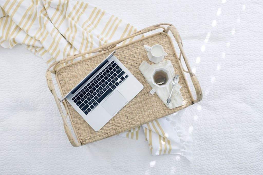 a wicker tray on a bed. The tray holds a laptop, a cup of tea, and milk for the tea.