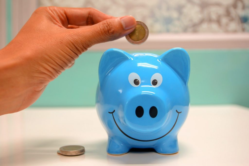 A close-up of a person's hand dropping a coin into a blue, smiling piggy bank.